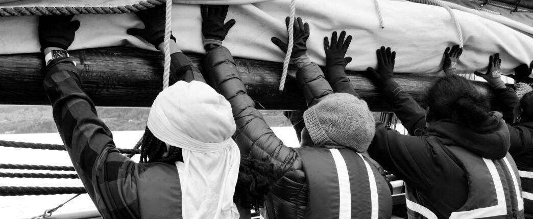 Rulling av seil krever mange hender.