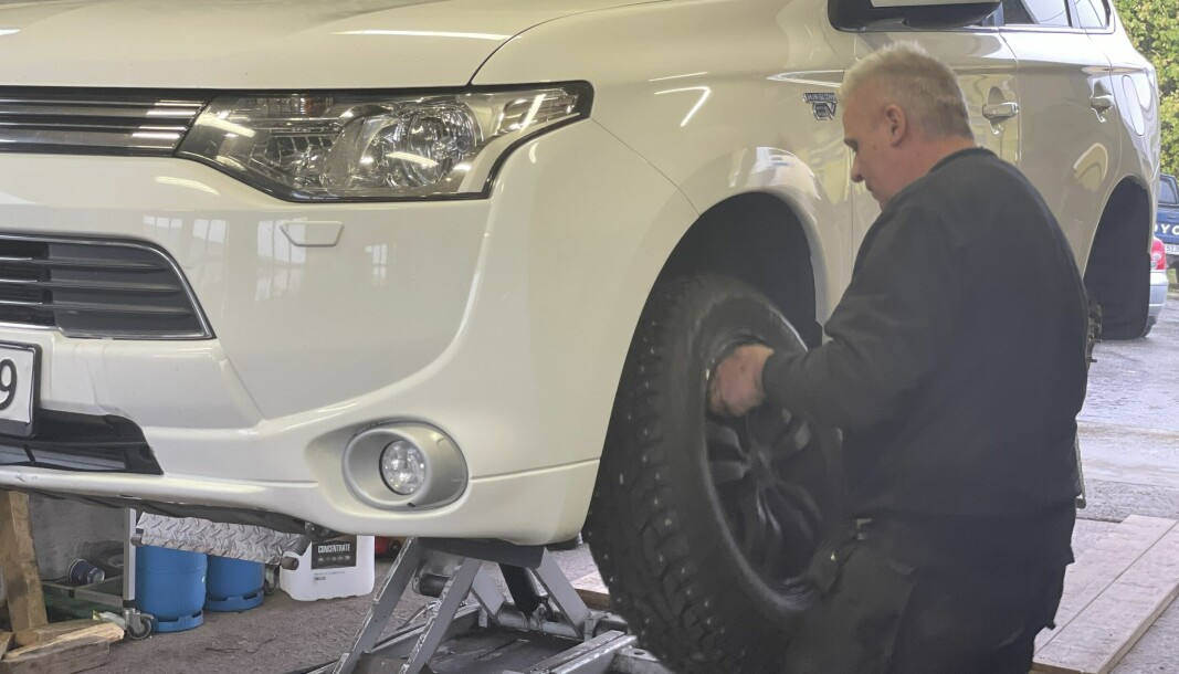 Her skifter Asbjørn Tore Humberset dekk på en bil som er inne.